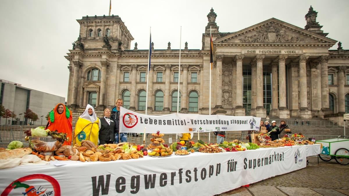 """Am heutigen Welternährungstag fand eine spektakuläre Aktion vor dem Bundestag statt, zu der MISEREOR in einem Bündnis mit anderen Organisationen aufgerufen hat. Eine 12 Meter lange Tafel wurde trotz anhaltendem Regen aufgebaut, zu der Abgeordnete aller Fraktion für ihre Mittagspause eingeladen worden waren. Auf der Tafel waren Lebensmittel arrangiert, die alle von """"Foodsharern"""" in Berliner Super-und Biomärkten gesammtelt hatten. Ohne diese Aktion wären alle Lebensmittel auf dem Müll gelandet."""